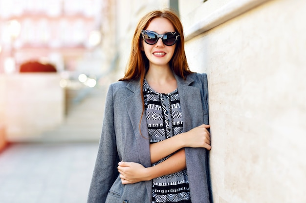Retrato do estilo de vida de mulher, usando vestido elegante glamour e óculos de sol vintage, tons quentes em tons, humor positivo.