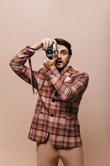 Retrato do estilo de vida de um jovem fotógrafo com blazer xadrez vintage e calças segurando a câmera e tirando fotos