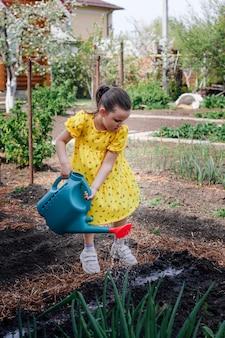 Retrato do estilo de vida de uma garota com um vestido regando um jardim com sementes de vegetais recém-plantadas.