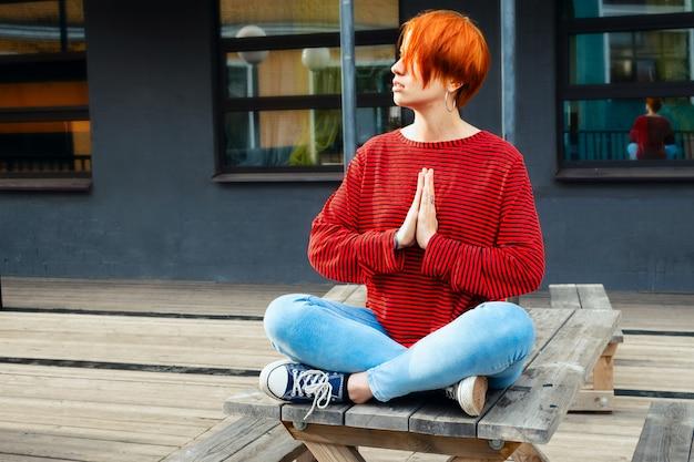 Retrato do estilo de vida de uma jovem mulher branca adulta com cabelo vermelho tingido, meditando sobre a mesa de madeira com gesto namaste. foco seletivo