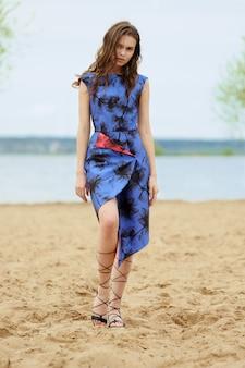 Retrato do estilo de vida de uma jovem mulher caminhando na areia no vestido azul com estampas.