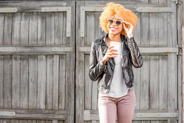 Retrato do estilo de vida de uma mulher africana em pé de jaqueta de couro com uma xícara de café ao ar livre no fundo da parede de madeira.