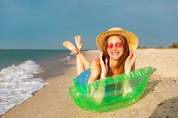 Retrato do estilo de vida de uma mulher loira de beleza feliz deitada no colchão de ar tomando banho de sol na praia, sorrindo e aproveitando as férias de verão