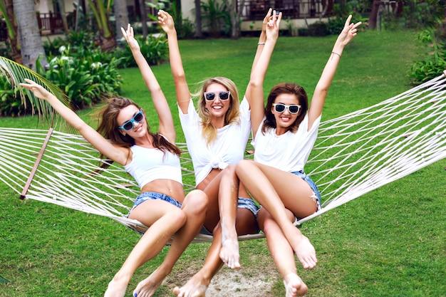 Retrato do estilo de vida de verão das mulheres da árvore enlouquecendo, gritando, rindo, se divertindo juntos, pulando na rede. usando tops brancos e óculos escuros, pronto para festa, alegria, diversão.