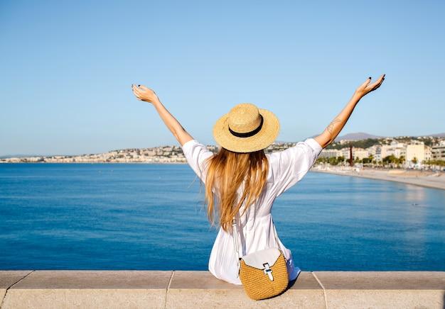 Retrato do estilo de vida de verão de uma turista loira posando em um mirante na riviera francesa