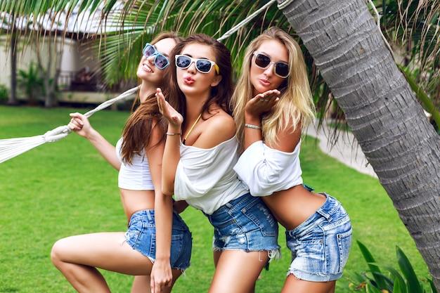 Retrato do estilo de vida de verão dos amigos de uma bela jovem árvore se divertindo juntos em um belo dia de verão no país tropical, três mulheres desfrutam de suas férias, prontas para a festa.