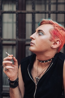 Retrato do estilo de vida do cigarro de fumo de homem gay com expressão facial satisfeita