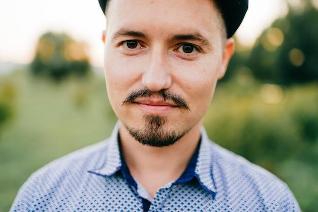 Retrato do estilo de vida do close up do homem cazaque considerável que levanta no verão ao ar livre no fundo abstrato da natureza. sorrindo feliz homem com bigode e barba boné. carismático adulto cara de camiseta azul