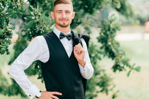Retrato do estilo de vida do noivo feliz posando ao ar livre na natureza