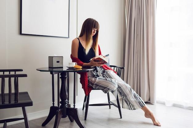 Retrato do estilo de vida interior de uma mulher linda morena lendo livro