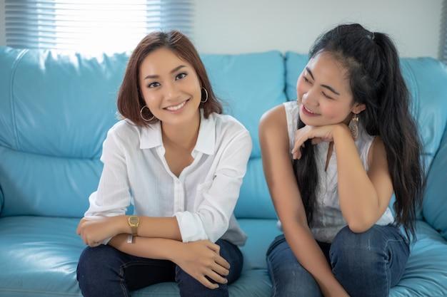 Retrato do estilo de vida mulheres asiáticas dos melhores amigos - sorrindo feliz no sofá na sala de estar