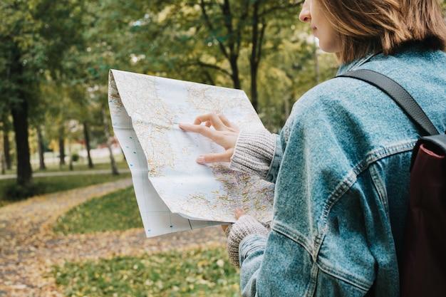 Retrato do estilo de vida na parte de trás da fêmea adulta jovem na floresta, segurando o mapa nas mãos dela,