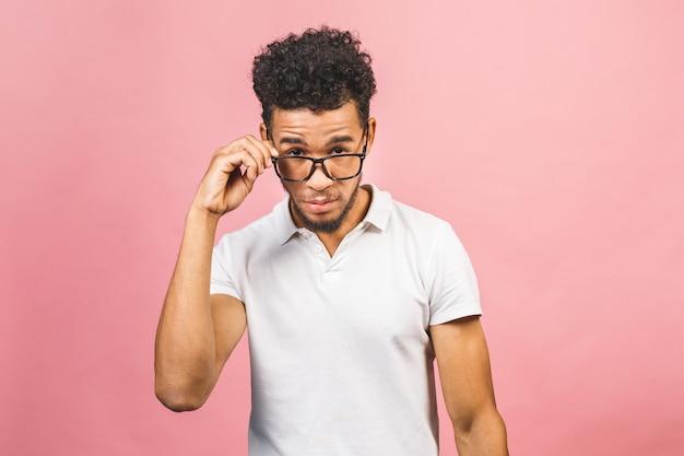 Retrato do estudante masculino africano fresco e considerável que olha a câmera que sorri com os monóculos isolados contra o fundo cor-de-rosa.