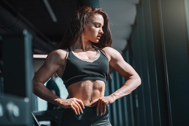 Retrato do fisiculturista feminino caucasiano bonito posando com as mãos nos quadris no ginásio e olhando para baixo. hoje dolorido. amanhã forte.