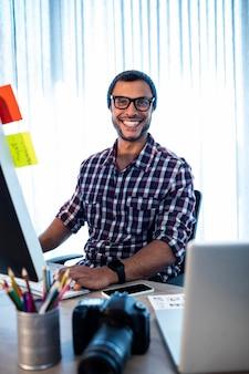 Retrato do fotógrafo de homem hipster sorrindo enquanto está sentado na mesa