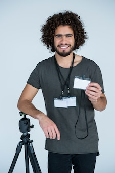 Retrato do fotógrafo masculino mostrando o bilhete de identidade
