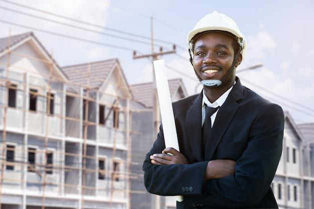 Retrato do gerente africano do engenheiro industrial do sorriso que está com o edifício
