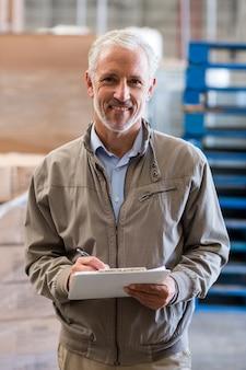 Retrato do gerente de armazém sorridente segurando uma prancheta