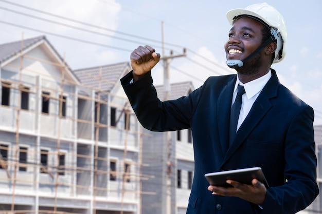 Retrato do gerente de engenheiro industrial africano de sucesso em pé com o edifício