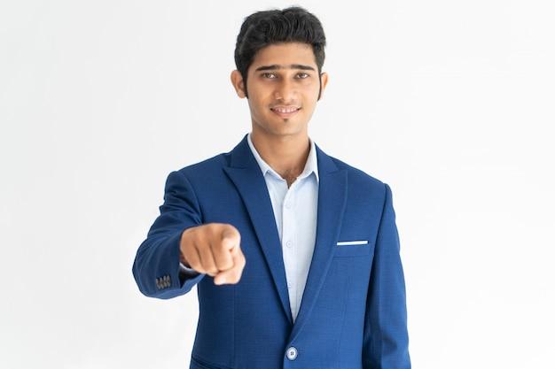 Retrato do gerente feliz que aponta na câmera com dedo indicador.