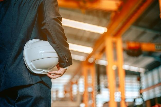 Retrato do gerente inspetor com capacete de segurança e usando máquinas de óculos na oficina da fábrica engenheiro
