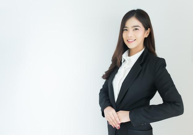 Retrato do gesto de acolhimento asiático novo da mulher de negócio sobre o fundo branco.