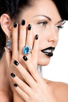 Retrato do glamour feminino com unhas, lábios e olhos pintados de preto