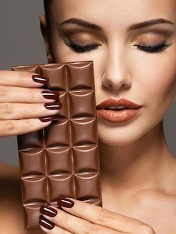 Retrato do glamour mulher bonita com unhas marrons segurando barra de chocolate