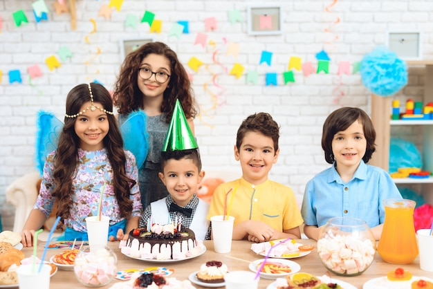 Retrato do grupo de crianças alegres na festa de anos.