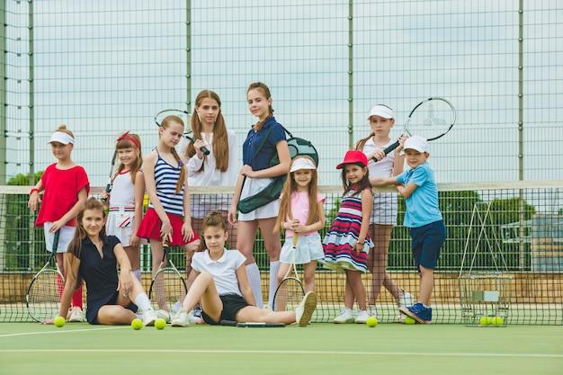 Retrato do grupo de meninas e menino como jogadores de tênis que mantêm raquetes de tênis contra a grama verde da corte ao ar livre.