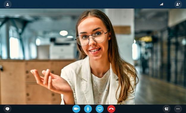 Retrato do headshot tela do aplicativo da trabalhadora em entrevista online usando webconferência no computador, jovem empresária falando por videochamada no laptop com um parceiro de casa