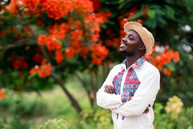 Retrato do homem africano que veste colorido tradicional de pano nativo com sorriso e feliz.