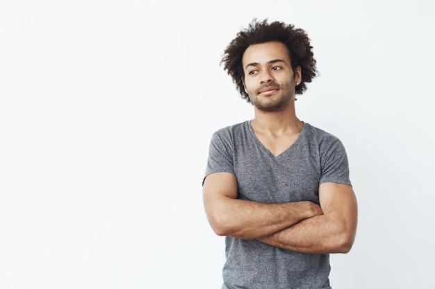 Retrato do homem africano stong e bonito que olha o levantamento esquerdo com os braços cruzados sobre a parede branca. conceito de inicialização confiante.
