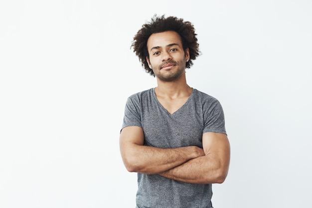 Retrato do homem africano stong e considerável que levanta com os braços cruzados sobre o fundo branco. empresário confiante ou estudante.