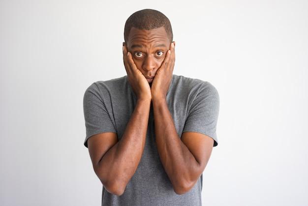 Retrato do homem afro-americano chocado e confundido.
