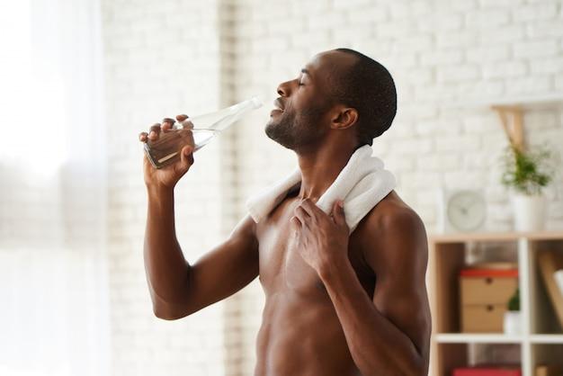 Retrato do homem afro-americano com água potável de toalha.