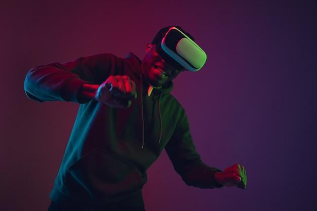 Retrato do homem afro-americano em vr-headset isolado no fundo gradiente do estúdio em luz de néon. lindo modelo masculino. conceito de emoções humanas, expressão facial, vendas, anúncio, inclusão, tecnologia.