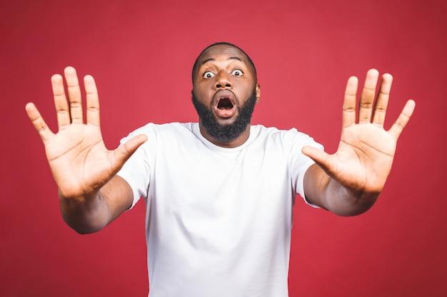 Retrato do homem afro-americano que guarda a mão no sinal de stop, advertindo e impedindo-o de algo ruim, olhando a câmera com expressão preocupada.