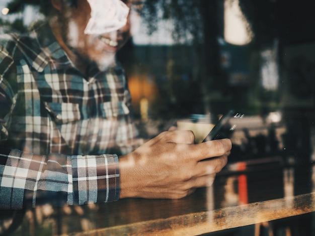 Retrato do homem asiático em usar a cafetaria esperta do telefone.