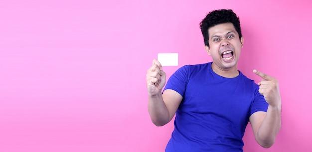 Retrato do homem asiático feliz que mantém o cartão de crédito isolado na parede cor-de-rosa.