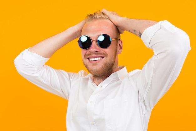 Retrato do homem atrativo de sorriso do europeu na camisa de vestido branca no amarelo.
