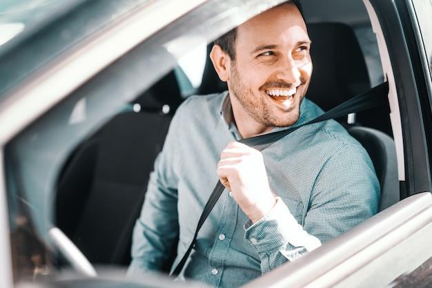 Retrato do homem caucasiano de sorriso que prende o cinto de segurança e sentado em seu carro. janela aberta, vista lateral.