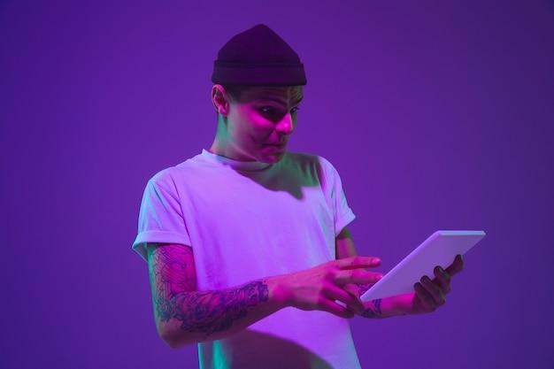 Retrato do homem caucasiano isolado no fundo do estúdio gradiente na luz de neon