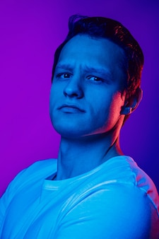 Retrato do homem caucasiano sobre fundo azul roxo em luz de néon multicolorida.