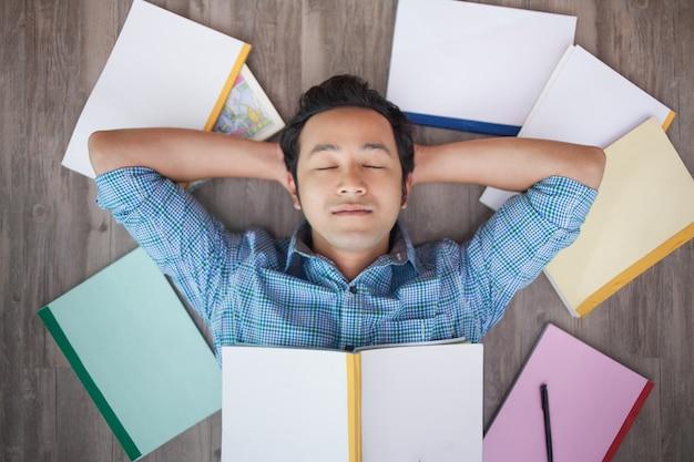 Retrato do homem cochilando asiática no assoalho entre livros