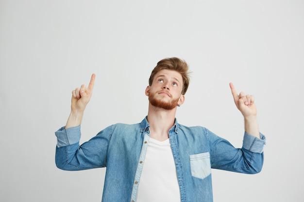 Retrato do homem considerável novo alegre que sorri apontando o dedo acima.