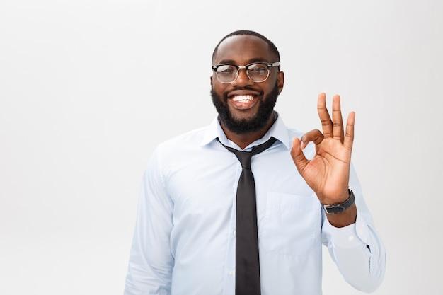 Retrato do homem de negócio afro-americano que sorri e que mostra o sinal aprovado. conceito de linguagem corporal