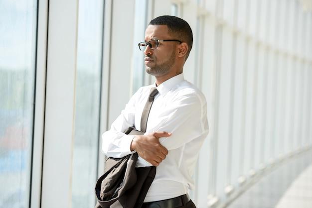 Retrato do homem de negócios africano novo no centro do escritório.