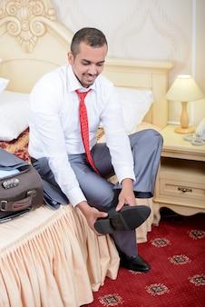 Retrato do homem de negócios asiático com a mala de viagem, sentando-se na cama.