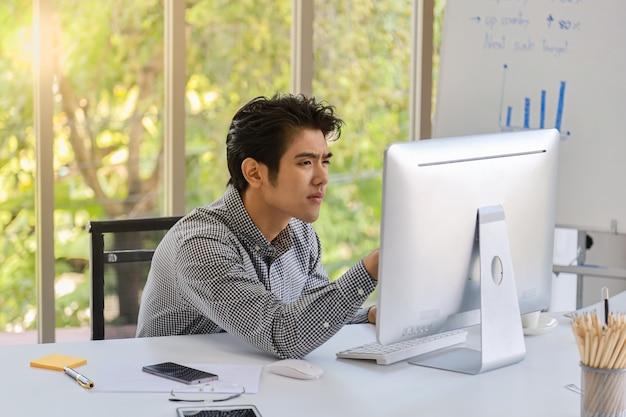 Retrato do homem de negócios asiático novo esperto que senta-se trabalhando e olhando para monitorar o computador de secretária com placa, telefone móvel, nota, original, vidros de leitura e pena de reunião no escritório.